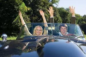 a couple raising hands inside a Jaguar E-Type convertible