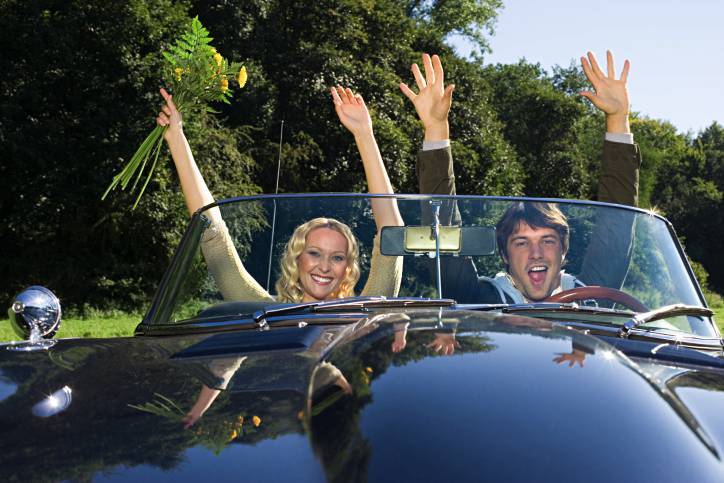 Couple in convertible with arms raised