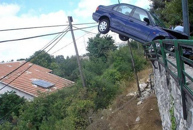 A crashed car on a bridge railing
