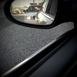 View of a police car from a side view mirror