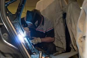 A welder working on a damaged car