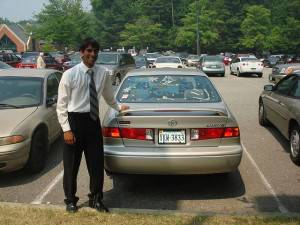 Sales person standing behind a car in his inventory