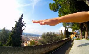 A raised hand with a panoramic street background