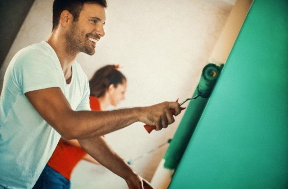 man and womain painting a wall green