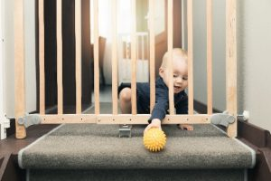 baby reaching through a gate for a toy